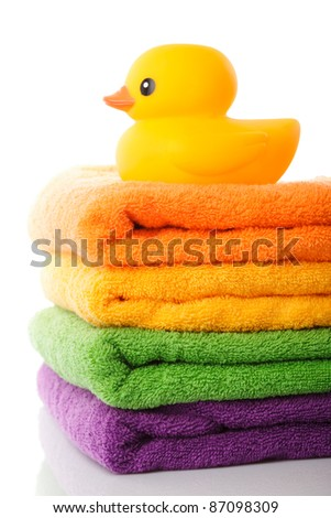 Stack of colorfull towels and yellow rubber duck isolated on white