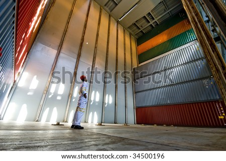 stack of containers in cargo hold of a large container ship (no trademarks visible) - stock photo