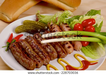 Stack of cooked sausages with red hot chilli peppers on a plate - stock photo