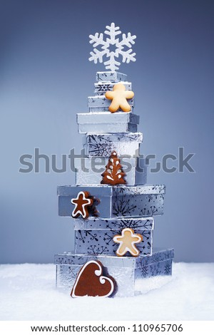 Stack of cool toned Christmas gifts in snow with crunchy gingerbread cookies and a snowflake depicting the winter season - stock photo