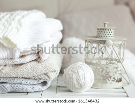 Stack of cozy knitted sweaters and lantern on a table - stock photo