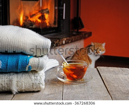 Stack of cozy knitted sweaters on a old wooden table, near fireplace and a cat sitting on the floor. warm concept - stock photo