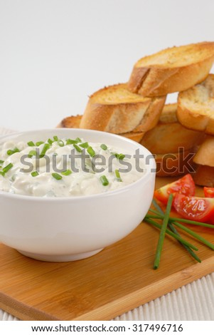 stack of croutons and bowl of chives spread on wooden cutting board