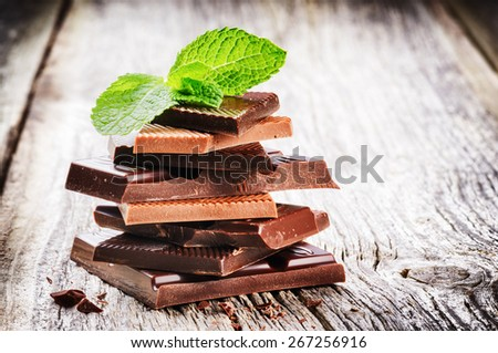 Stack of dark and milk chocolate pieces with mint leaf  - stock photo