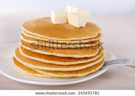 Stack of delicious pancakes with butter on table and light background