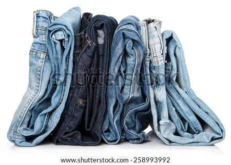 Stack of different blue jeans on white background - stock photo