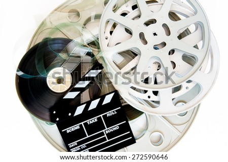 Stack of different movie film reels with clapper board on white background - stock photo