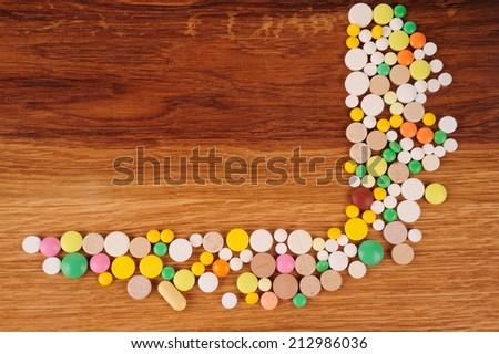 Stack of different pills in  on wooden desk - stock photo