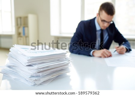 Stack of documents on the desk and male employee working on background - stock photo