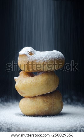 Stack of Donuts sprinkled with sugar over dark background - stock photo