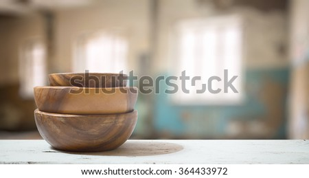 stack of empty wooden bowls old white table in the living room - stock photo