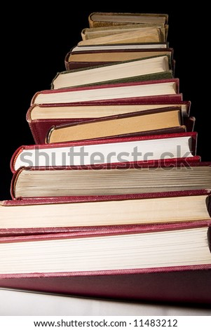 Stack of encyclopedia books over black background, photo from under the stack - stock photo