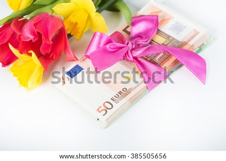 Stack of euro associated with a pink ribbon - stock photo