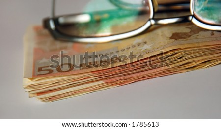 stack of euro bills under business glasses - stock photo