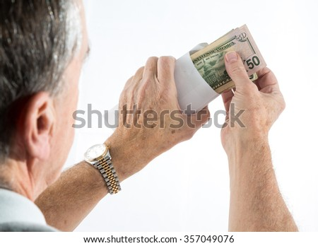 Stack of fifty and twenty US dollar bills being put in envelope by senior caucasian hands with side view of head as though looking over shoulder