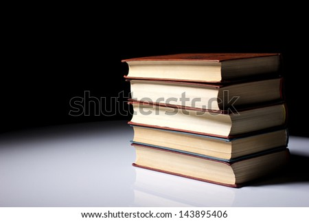 stack of five old  books on white table on black background