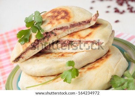 Stack of flat bread with red beans and coriander