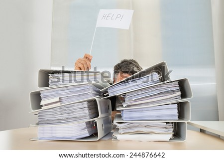 Stack Of Folders In Front Of Businessman Holding White Flag With Help Text - stock photo