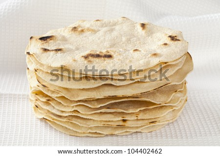 Stack of fresh corn tortillas in a white cloth.