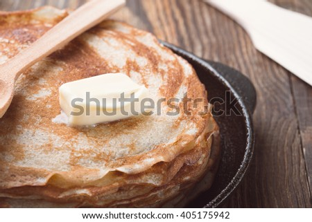 Stack of fresh homemade crepes with butter on top on cast iron pan for brunch or dessert  on a  rustic wooden table - stock photo