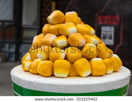 Stack of freshly baked bread rolls in the form of a pyramid displayed on a round table at a catered event or fairground - stock photo