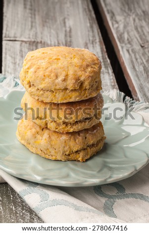 stack of freshly baked homemade pumpkin biscuits on an old barn wood table - stock photo