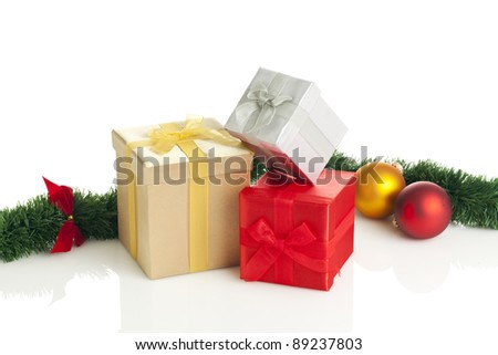 stack of gift boxes with christmas baubles and garland on white background