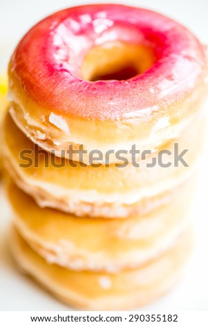 Stack of Glazed Doughnuts with colourful sprinkles, chocolate, icing on top of them. White background. Selective focus. Narrow DOF - stock photo