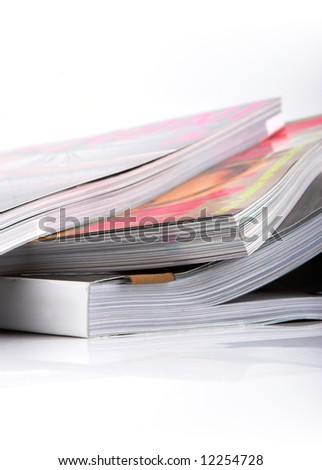 Stack of glossy magazines on a white background.