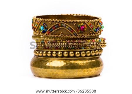 stack of golden bracelets isolated on white background - stock photo