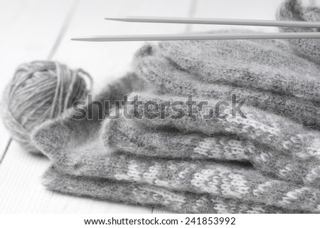 Stack of gray warm fluffy knitwear with knit needles and ball on white wood. - stock photo