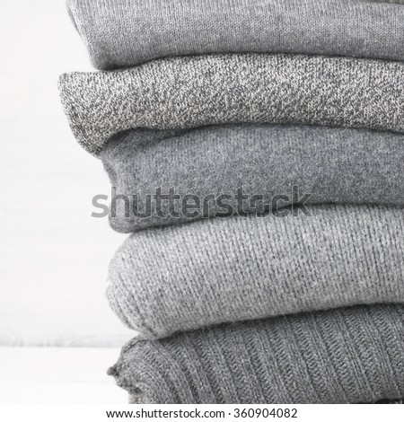 Stack of gray woolen knitted sweaters close-up. - stock photo