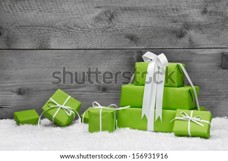 Stack of green Christmas presents, with snow on grey wooden background - stock photo
