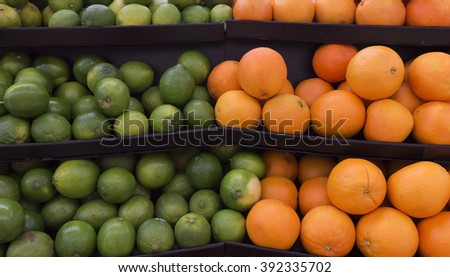Stack of green lime and oranges on shelf