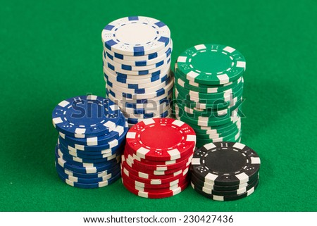 Stack of green, red, blue, white and black Playing Poker Chips in a green background