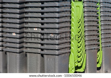 stack of grey waste bins with green lid - stock photo