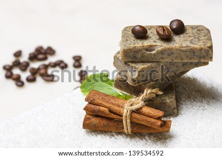 Stack of handmade flavored soap bars with coffee beans, cinnamon and lavender leaf on white towel. - stock photo