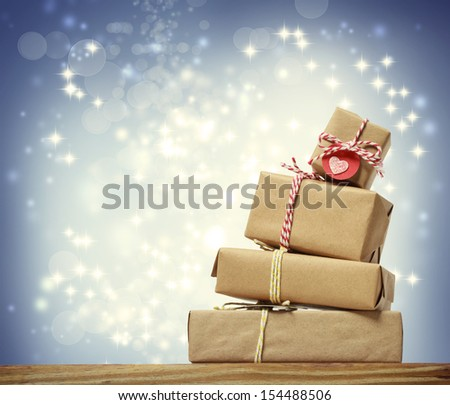 Stack of handmade gift boxes over snowing night background - stock photo