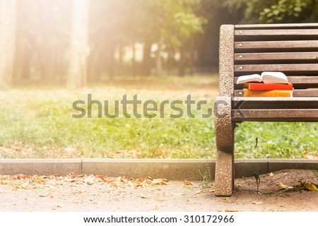 Stack of hardback book and Open book lying on a bench at sunset  park on blurred nature  backdrop. Copy space, back to school. Education background. - stock photo