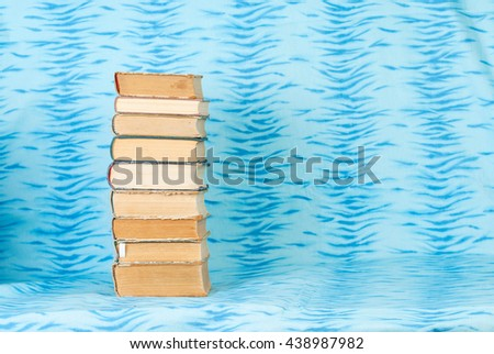 Stack of hardback books on blue cloth. Back to school. Copy space - stock photo
