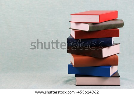 Stack of hardback books on blue table. Back to school. Copy space. - stock photo