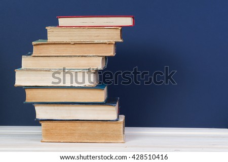 Stack of hardback books on wooden table. Back to school. Copy space. - stock photo