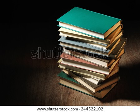 Stack of hardcover books arranged haphazardly viewed from a high angle on a wooden desk or table with copyspace and shadow behind - stock photo