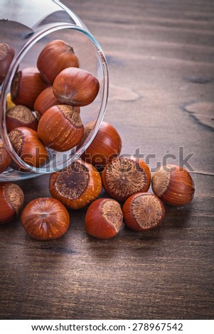 stack of hazelnuts in glass bowl on vintage wooden board food and drink still life  - stock photo