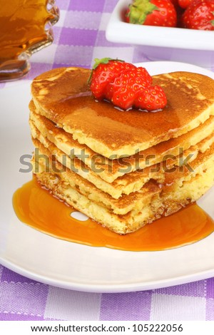 Stack of heart shaped pancakes with syrup and a strawberry on a white dish. A perfect breakfast for Valentine's Day.