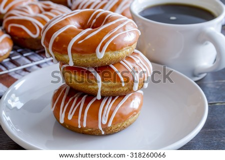 Stack of homemade baked pumpkin donuts with orange pumpkin glaze sitting on white plate with cup of coffee - stock photo