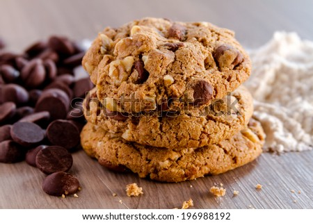 Stack of homemade chocolate chip cookies sitting in front of ingredients - stock photo