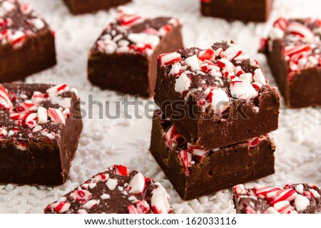 Stack of homemade peppermint fudge sitting on white glitter snowflakes - stock photo