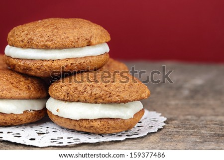Stack of homemade Pumpkin Whoopie Pies or Moon Pies made with cream cheese frosting.  - stock photo