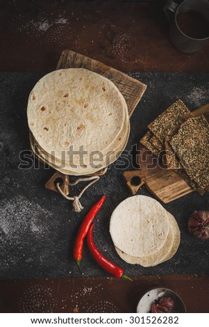 Stack of homemade tortilla and crust tortilla on vintage cutting board with chili red pepper, from above on dark stone table. Rustic dark style - stock photo